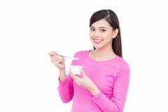 Ung asiatisk kvinnlig tyckande om smak av yoghurten som isoleras på vit Royaltyfri Bild