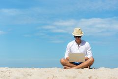 Ung asiatisk man för livsstil som arbetar på bärbara datorn, medan sitta på den härliga stranden, frilans- arbete på feriesommar, royaltyfri fotografi