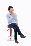Ung asiatisk man som är tänkande på stolen. fotografering för bildbyråer