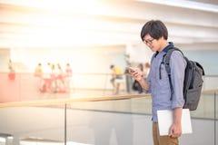 Ung asiatisk man som använder smartphonen i shoppinggalleria royaltyfria bilder