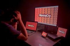 Ung asiatisk man som frustreras av WannaCry ransomwareattack Fotografering för Bildbyråer