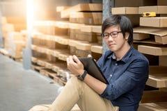 Ung asiatisk man som gör inventering, genom att använda minnestavlan i lager royaltyfri foto