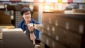 Ung asiatisk man som gör inventering, genom att använda minnestavlan i lager arkivfoto