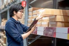Ung asiatisk man som gör inventering, genom att använda minnestavlan i lager arkivbilder