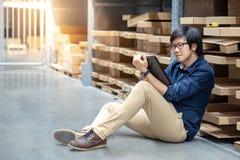 Ung asiatisk man som gör inventering, genom att använda minnestavlan i lager royaltyfria foton