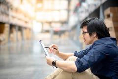 Ung asiatisk man som gör inventering i lager arkivbild