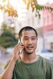 Ung asiatisk man som har en konversation på hans mobiltelefon utanför Arkivbild