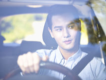 Ung asiatisk man som kör en bil arkivfoton