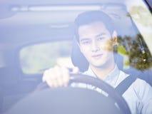 Ung asiatisk man som kör en bil arkivbilder
