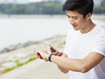 Ung asiatisk man som kontrollerar mobiltelefonen och klockan för övning Royaltyfri Fotografi