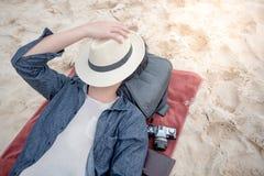 Ung asiatisk man som ligger på stranden, slutframsida vid hatten arkivbild