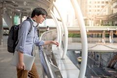 Ung asiatisk man som ser runt om gatan, stads- livsstil royaltyfri fotografi