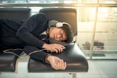 Ung asiatisk man som sover på bänk i flygplatsterminal Royaltyfri Bild
