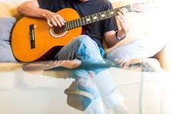Ung asiatisk man som spelar den spanska gitarren inomhus arkivbild