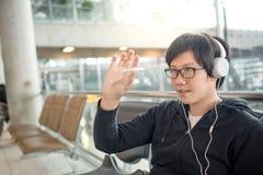 Ung asiatisk man som spelar spinnarerastlös människa i flygplatsterminal royaltyfria bilder