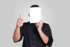 Ung asiatisk man som täcker hans framsida med lilla Whiteboard royaltyfri bild