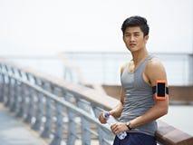 Ung asiatisk man som tar ett avbrott under utomhus- övning Royaltyfria Foton