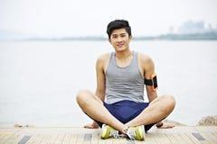 Ung asiatisk man som tar ett avbrott under utomhus- övning Arkivfoton