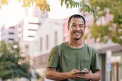 Ung asiatisk man som utanför överför en text på hans mobiltelefon Arkivfoton