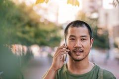 Ung asiatisk man som utanför talar på hans mobiltelefon Arkivfoto