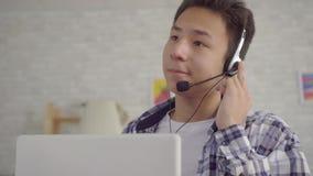 Ung asiatisk manarbetare för stående i hörlurar som talar den konsulterande klienten för appell, begrepp av att arbeta hemifrån arkivfilmer