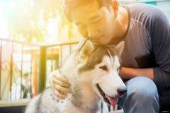Ung asiatisk manlig hundägare som kramar och omfamnar det Husky Siberian hundhusdjuret med förälskelse och omsorg royaltyfri foto