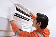 Ung asiatisk manlig tekniker som reparerar luftkonditioneringsapparaten med skruven Royaltyfria Foton