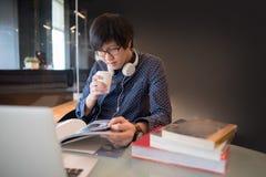 Ung asiatisk manuniversitetsstudentläsebok i arkiv royaltyfri bild