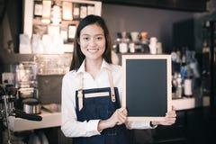 Ung asiatisk meny för svart tavla för mellanrum för kvinnabaristainnehav i coffe royaltyfri foto