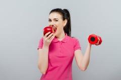 Ung asiatisk muskulös kvinnautbildning och äpple av handen med röda hantlar, kg Arkivbild