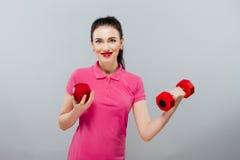 Ung asiatisk muskulös kvinnautbildning och äpple av handen med röda hantlar, kg Fotografering för Bildbyråer