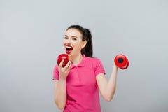 Ung asiatisk muskulös kvinnautbildning och äpple av handen med röda hantlar, kg Arkivfoto