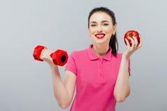 Ung asiatisk muskulös kvinnautbildning och äpple av handen med röda hantlar, kg Royaltyfria Foton