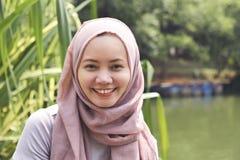 Ung asiatisk muslimkvinna i hijab med smileyframsidan Arkivbilder