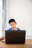 Ung asiatisk pojke som hemma använder bärbar datorteknologi Copyspace Arkivfoto