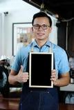 Ung asiatisk svart tavla och tumme för mellanrum för manbaristainnehav upp wi Royaltyfria Bilder