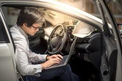Ung asiatisk tekniker eller arkitekt som arbetar med bärbara datorn i hans bil Arkivfoton