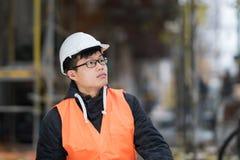 Ung asiatisk tekniker på arbete på konstruktionsplats Royaltyfri Foto