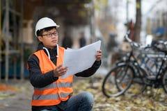 Ung asiatisk tekniker på arbete på konstruktionsplats Fotografering för Bildbyråer