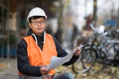 Ung asiatisk tekniker på arbete på konstruktionsplats Arkivbild