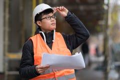 Ung asiatisk tekniker som arbetar på konstruktionsplats Arkivbilder