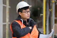 Ung asiatisk tekniker som arbetar på konstruktionsplats Arkivfoto