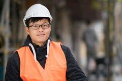 Ung asiatisk tekniker som ler på konstruktionsplats Arkivfoto