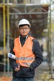 Ung asiatisk tekniker som poserar på konstruktionsplats Arkivbild