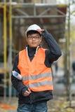 Ung asiatisk tekniker som poserar under hans arbete på konstruktionsplats Arkivfoton