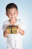 Ung asiatisk unge i sleepwear som rymmer en gåva Royaltyfri Bild