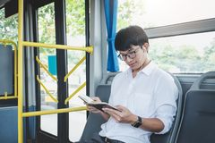 Ung asiatiskt manhandelsresandesammanträde på en lyssnande musik för buss och beträffande arkivfoto
