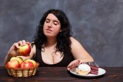 Ung attraktiv överviktig kvinna som väljer sunda foods och giv Arkivfoto