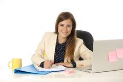 Ung attraktiv affärskvinna för företags stående på kontorsstol som arbetar på skrivbordet för bärbar datordator royaltyfri fotografi