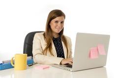 Ung attraktiv affärskvinna för företags stående på kontorsstol som arbetar på skrivbordet för bärbar datordator arkivbilder